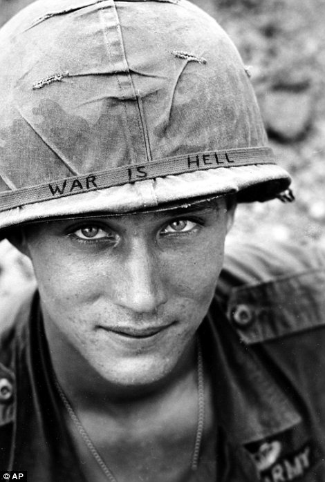 """An unidentified U.S. Army personnel wears a hand lettered """"War Is Hell"""" slogan on his helmet"""