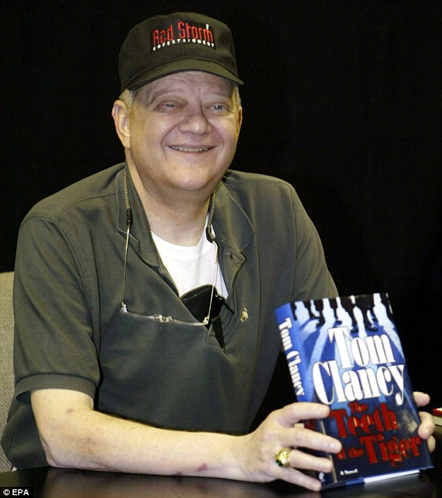 Tom Clancy poses with a copy of his novel 'The Teeth of the Tiger' during the book's presentation at Barnes and Nobles Books on Fifth Avenue in New York City in 2003