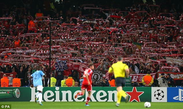 Flying the flag: Bayern fans hold aloft scarfs as they cheer their side on at the Etihad