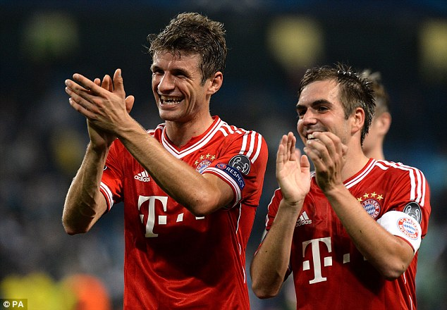 All smiles: Thomas Muller (left) and Philipp Lahm celebrate victory at the Etihad Stadium