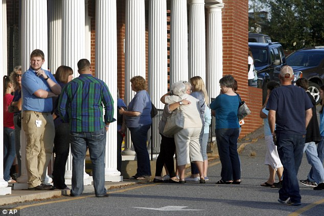 Tragedy: Members of the Front Street Baptist Church in North Carolina mourn after learning that six elderly members of their church died in a bus crash