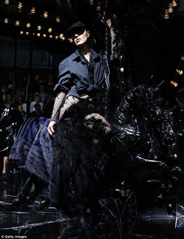 In the shadows: Eva rode a black horse on a merry-go-round during the stunning show