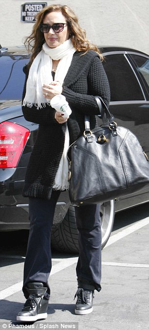 Hands full: Karina Smirnoff couldn't put the phone down while Leah Remini seemed saddled by her large tote and scarf