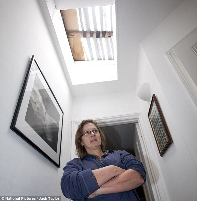 Repair bills: Catherine Seale, mother of Christopher, stands underneath the damaged skylight at her home
