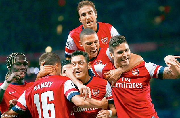 Mes-merising: Mesut Ozil is congratulated by his Arsenal team-mates following his stunning strike during Tuesday night's 2-0 win over Napoli in the Champions League