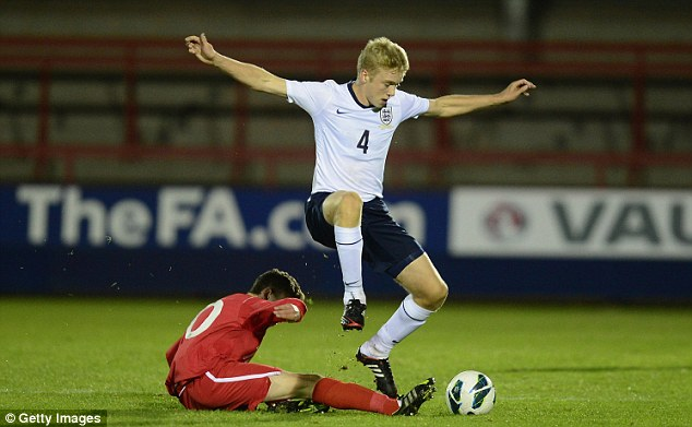 Halted: England's Tom Davies is tackled by Nathan Broardhead