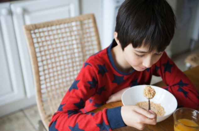 Boy eating breakfast cereal at table
