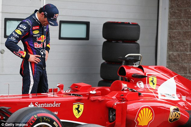 Once over: Red Bull's Mark Webber takes a closer look at the tyre damage on Alonso's car. It was a frustrating qualifying session for the Australian, who was handed a ten-place grid penalty