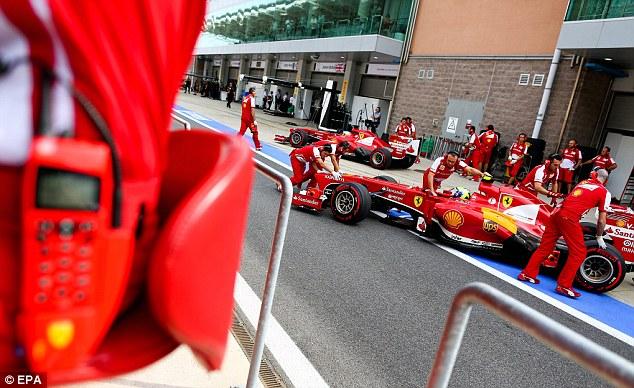 Plenty to work on: Ferrari mechanics push the cars of Alonso and teammate Felipe Massa back into the garage