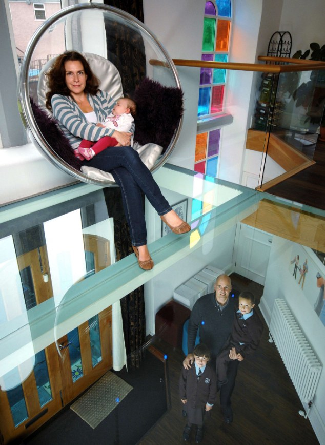 Seeing the light: Caroline and baby Mariella sit in the suspended bubble chair above the glass floor - beneath them are Mario, Angelina and Valentino in the hallway