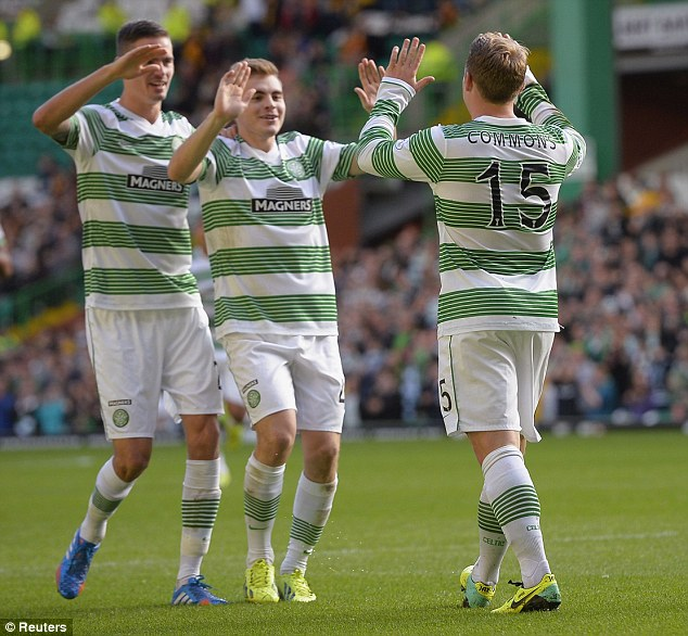 Flying high: Kris Commons celebrates scoring Celtic's second goal as they returned to the top of the Scottish Premiership table with a 2-0 win over Motherwell