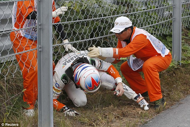 Assistance: Paul di Resta, who was forced to retire early, is helped under a fence by marshals