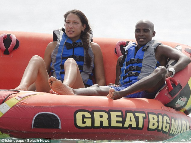 Hold on tight: Mo and Tania headed for some water sports action and was seen being hauled in a inflatable boat in the sea