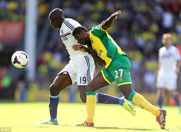 Heads you win: Demba Ba (left) gets to the ball a fraction ahead of Norwich's Alexander Tettey