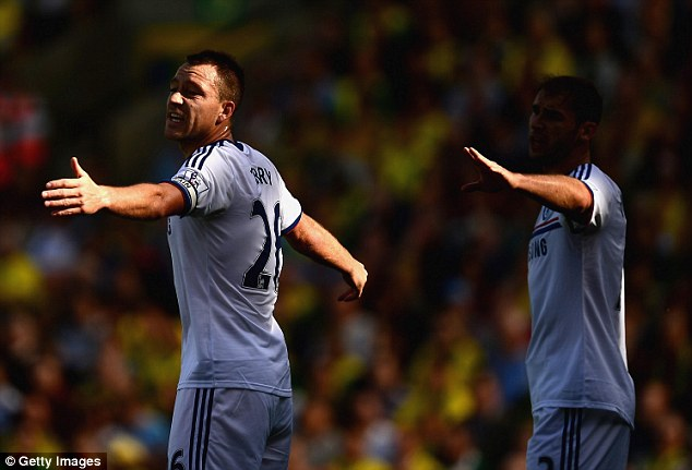 Trick of the light: John Terry and Branislav Ivanovic marshal the Chelsea defence in the shadows