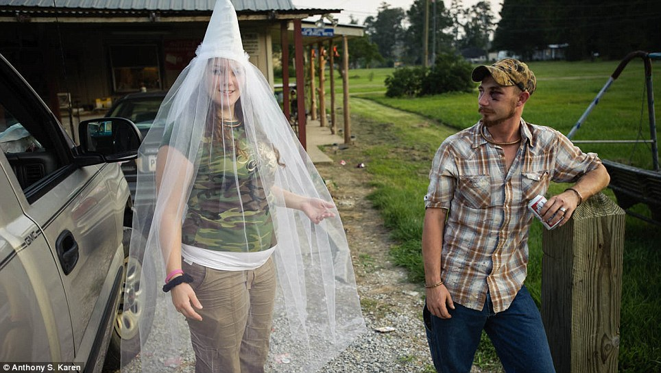 White power wedding: 'Little Charlie' shows off her custom made Klan wedding veil as her fiancé watches on. These photographs show the little-seen rituals and home lives of the far-right organisation