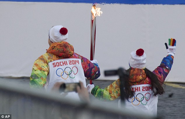 Young Russian figure skaters Lina Fedorova, right, and Maxim Moroshkin carry the Olympic torch