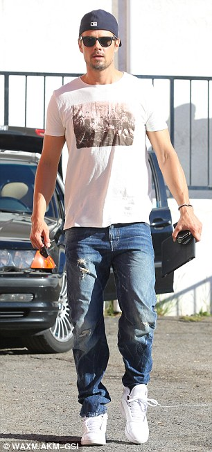 Stylish dad: The Safe Haven star was casually cool in ripped jeans and a white printed T-shirt