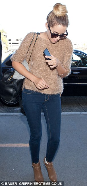 Jet setter: The 27-year-old designer dressed for comfort in a beige fuzzy jumper, blue skinny jeans, and brown booties