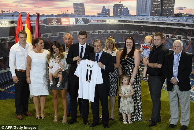Centre of attention: Bale stands with Madrid's President Florentino Perez and his family after making the move