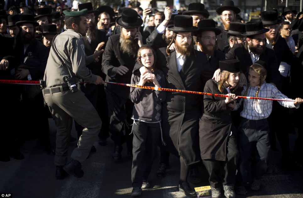 Struggle: An Israeli border police officer tries to stop orthodox men and children from reaching the vehicle