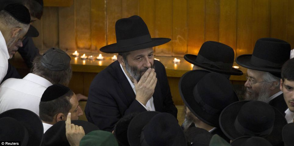 Arye Deri (centre), leader of the ultra-religious Shas political party, looks on near the body of Rabbi Ovadia Yosef