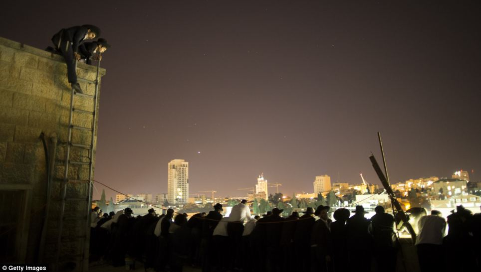 Jewish mourners observe the funeral from the rooftops as night descends