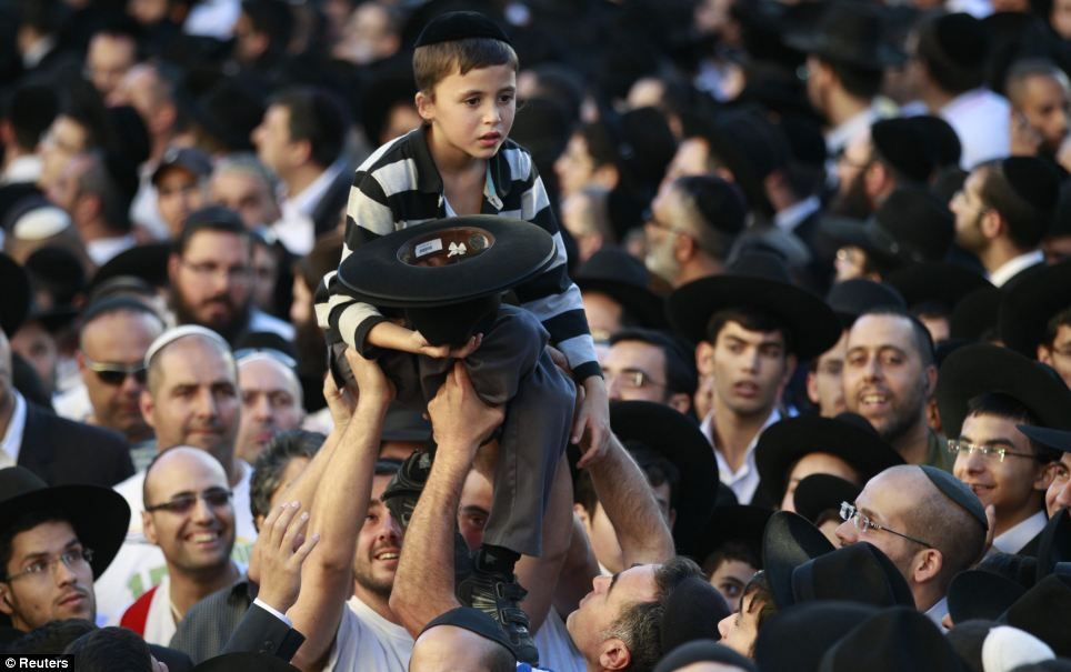 Overwhelmed: A little boy looks overwhelmed as he is carried over the crowds watching the body of a pivotal religious leader be carried through