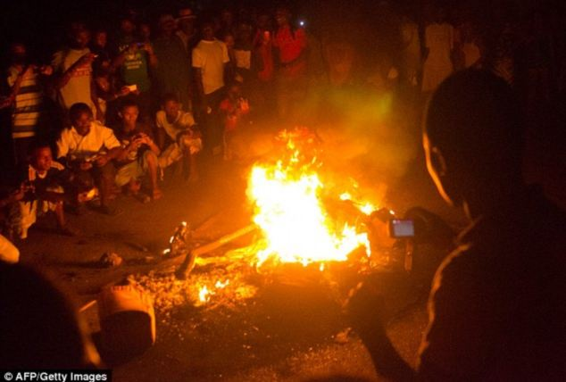 Crowds sat calmly beside the burning bodies while many filmed the killings before circulating the recordings