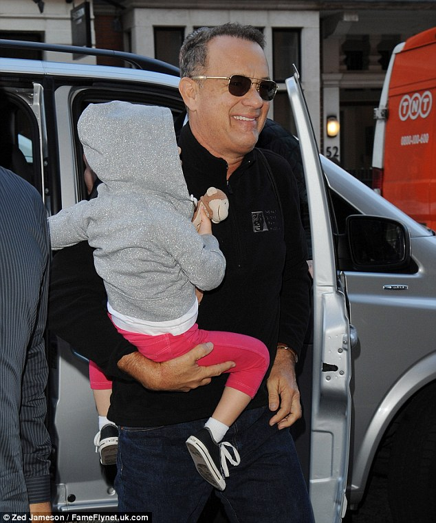 Tom Hanks pictured arriving at Claridges Hotel carrying his grandchild in in London on Tuesday after revealing he has been diagnosed with type 2 diabetes
