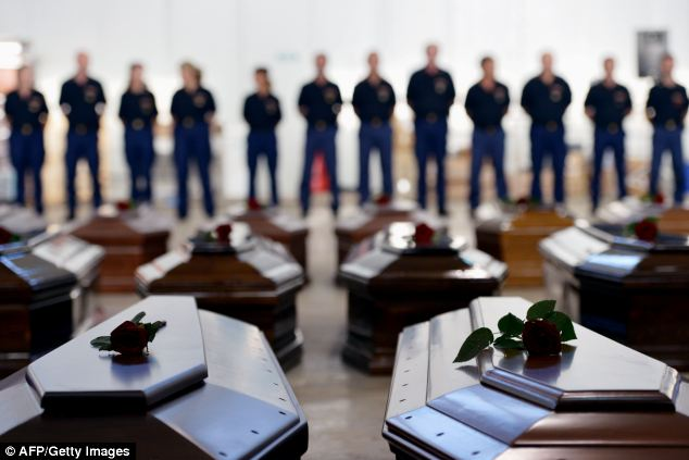 Grim: People stand next to coffins of victims in a hangar of the Lampedusa airport