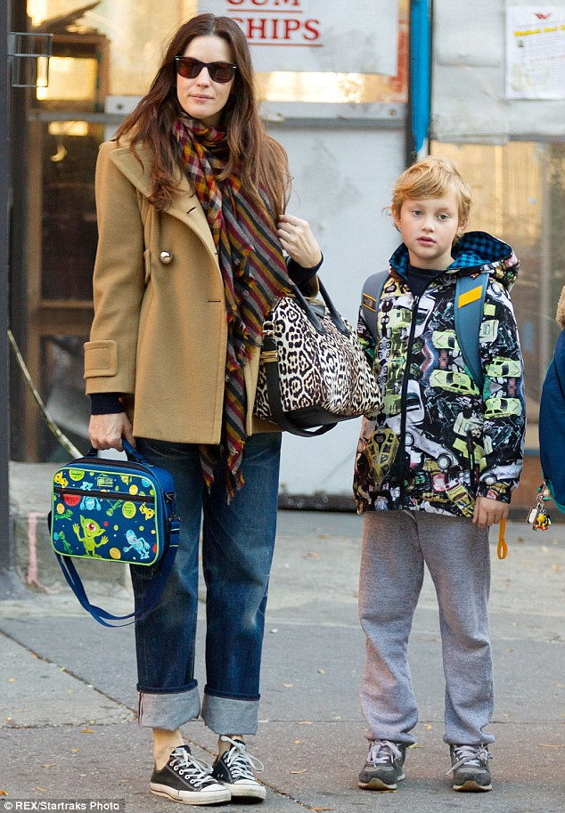 Bundled up: Liv Tyler was ready for a New York winter in her warm, striped scarf and woolly jacket as she picked up her son Milo from school on Tuesday