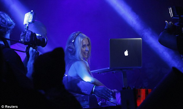 Work hard party hard: Paris didn't seem to mind taking to the DJ decks at her own bash as she donned some sparkly headphones for a set