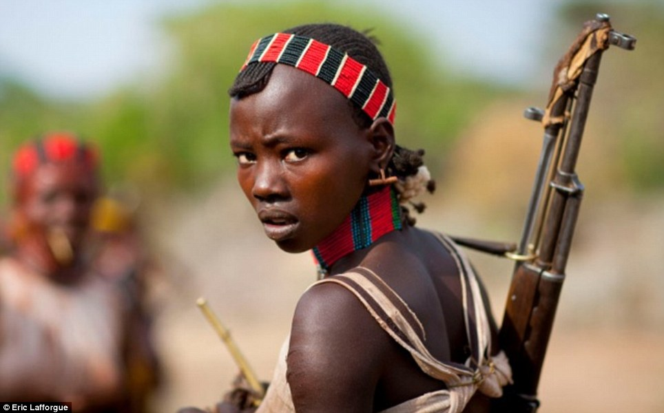 Protection: This Hamar girl's battered old rifle contrasts starkly with her beauty and spectacular beaded necklace and headband