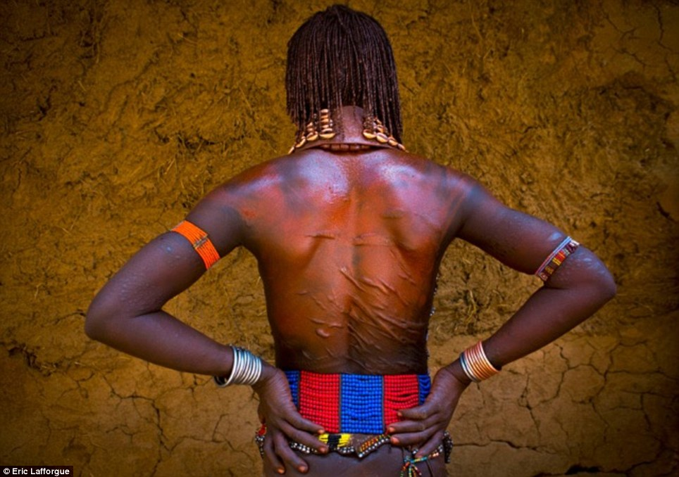 Brutal: Hamar women volunteer to be beaten by 'Maza' (initiated men) during their brothers' coming of age ceremonies. They show off their scars with pride