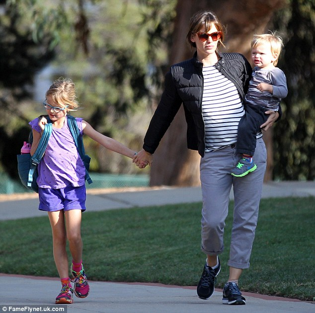 Three-of-a-kind: The busy mom-of-three juggled son Samuel on her hip as she walked hand-in-hand with eldest child Violet, who was looking sporty in her mismatched purple T-shirt and shorts and pink colourful shoes