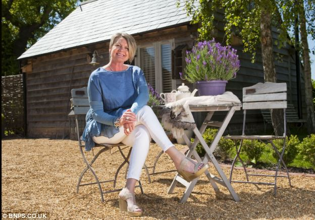 Idyll: Mrs Griffin-Rogers outside her renovated bolthole in Shropshire - which earns her £3,200 a month