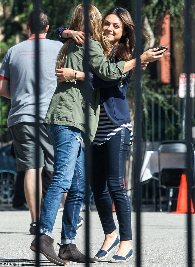 Big hug! Mila Kunis was all smiles as she embraced her female friend on a set in Hollywood