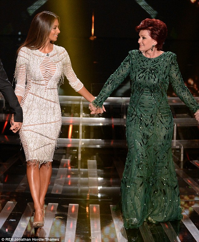 Hand in hand: Nicole and Sharon Osborne take to the stage in distinctive eighties inspired outfits