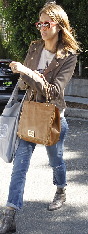 Going backwards and forwards: Jessica teamed her look with a large tan leather bag and a shopping bag from her own Honest Company, which she co-founded