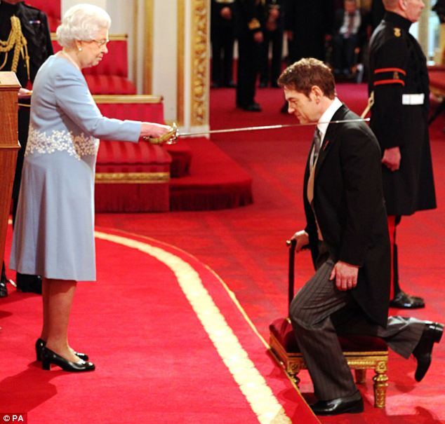 Actor Kenneth Branagh receiving a knighthood from Queen Elizabeth II