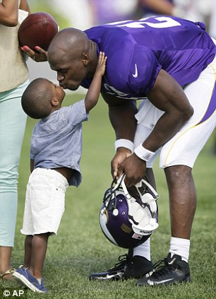 Minnesota Vikings running back Adrian Peterson gets a kiss from his son Adrian Jr. at the end of practice at NFL football training camp