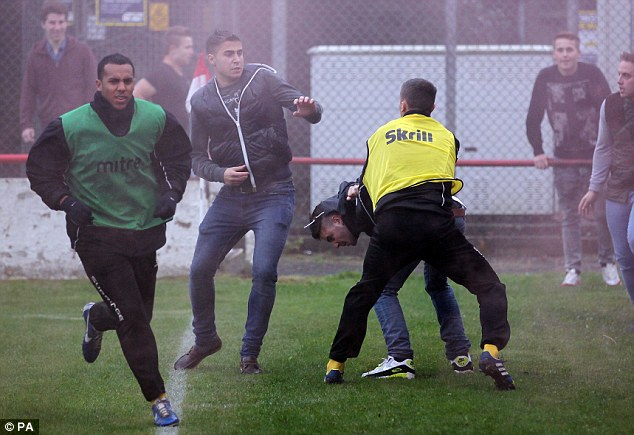 Scrap: Barrow substitute Greg Mills was attacked by some of the Atherstone supporters as he warmed up on the pitch during the half-time interval