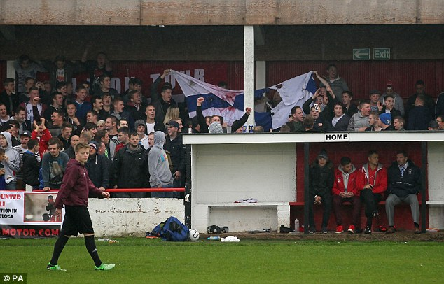 Torn apart: Atherstone Town 'fans' rip up a Barrow flag stolen from the away section after violence erupted during half-time in Saturday's FA Cup third qualifying round tie at Sheepy Road