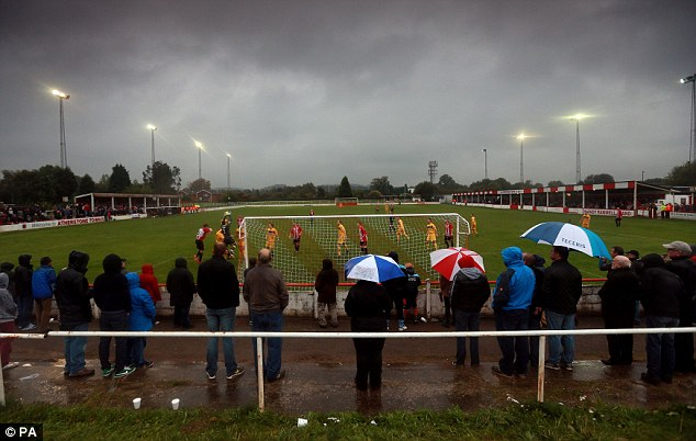 Soggy: The match at Sheepy Road was played out under floodlights because of the pouring rain