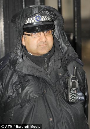 A police officer guards at the gates to Downing Street, drenched due to heavy rain