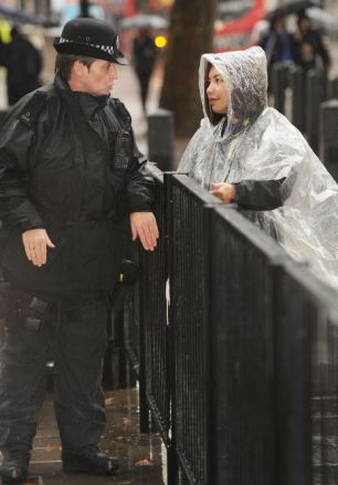 A police officer, completely drenched, talks to a member of the public at Downing Street