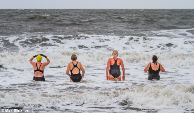 Very brave: Sunday morning swimmers enjoy wild waves in the cold weather on Portobello Beach in Edinburgh