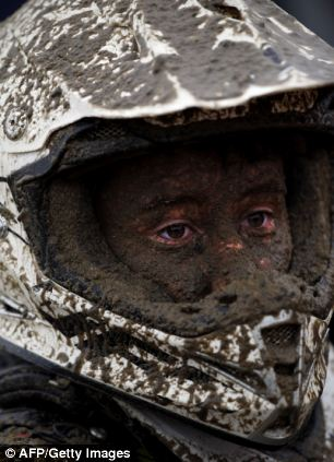 Covered: A quad biker's face is caped in mud following his race
