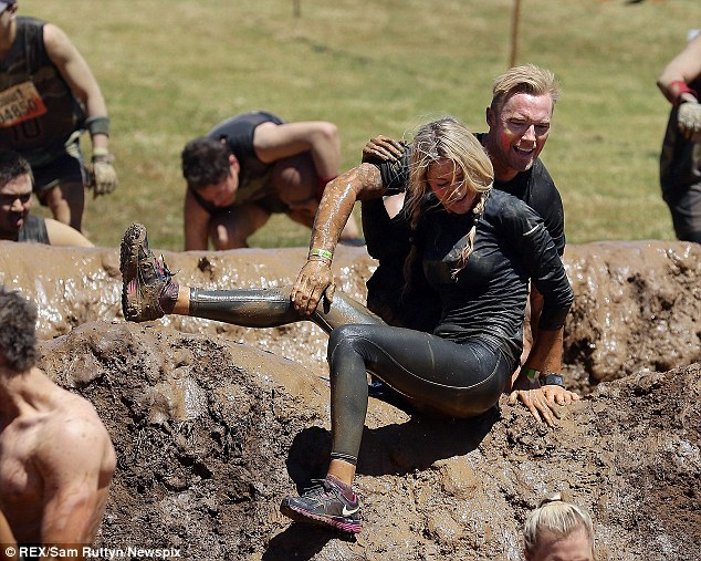 Helping hand: Ronan helps Storm get her leg over the muddy hill as they battle their way through the assault course